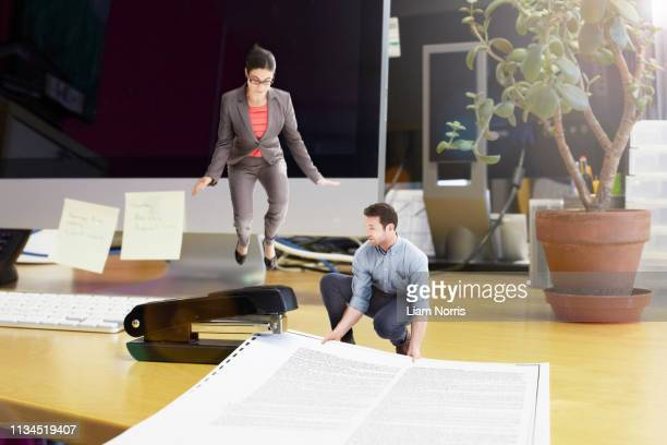 Mid adult business colleagues stapling large document on oversized desk