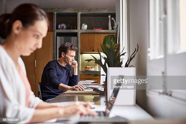 mid adult business couple working at desk - home office imagens e fotografias de stock