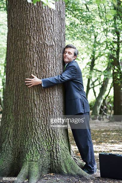 Mid adult business man hugging tree trunk, eyes closed