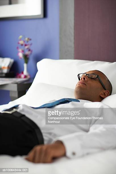 """mid adult business man lying on bed, differential focus - """"compassionate eye"""" fotografías e imágenes de stock"""
