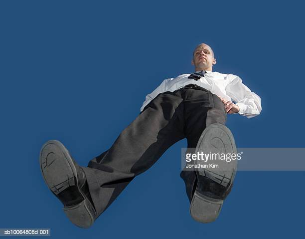 mid adult business man standing on glass, blue sky, view from below - 靴底 ストックフォトと画像