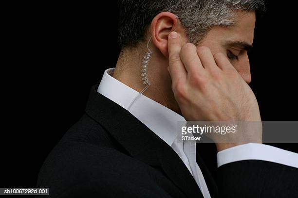 mid adult business man wearing hands-free device, close-up - watchmen stock pictures, royalty-free photos & images