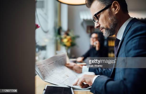 mid adult business professional reading newspaper in cafe - tenue d'affaires photos et images de collection