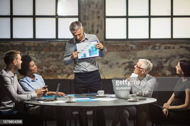 mid adult businessman analyzing charts with is colleagues on a meeting. - aiming stock pictures, royalty-free photos & images