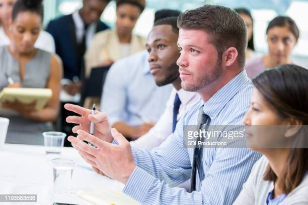 mid adult businessman asks question during meeting - town hall meeting stock pictures, royalty-free photos & images