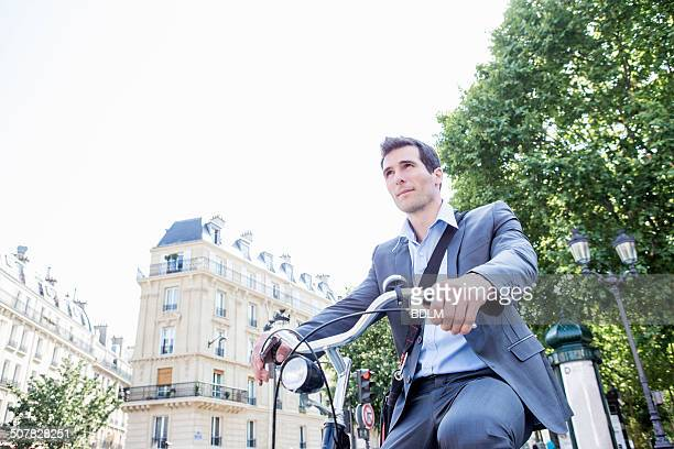 Mid adult businessman commuting on bicycle, Paris, France