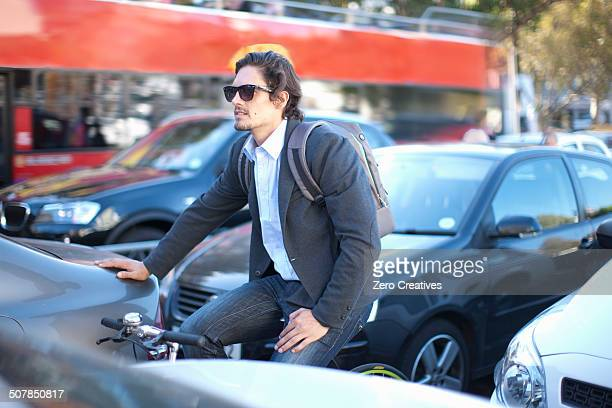 Mid adult businessman cycling during rush hour