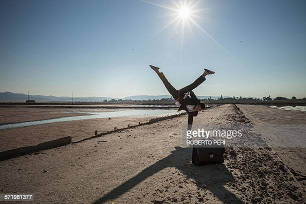 Mid adult businessman doing handstand on beach