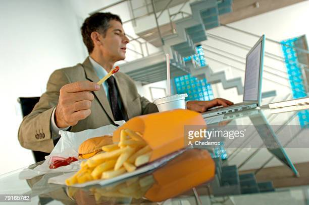 Mid adult businessman eating French fries, using laptop