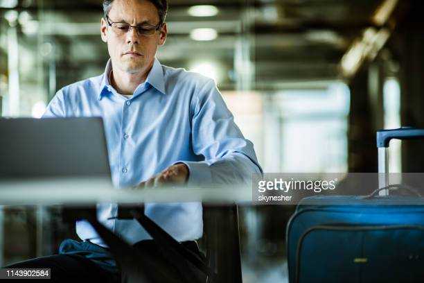 mid adult businessman finishing his work before going in a trip. - economist stock pictures, royalty-free photos & images