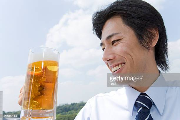 Mid adult businessman holding mug of beer