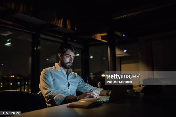 mid adult businessman in office at night typing on laptop - working overtime stock pictures, royalty-free photos & images