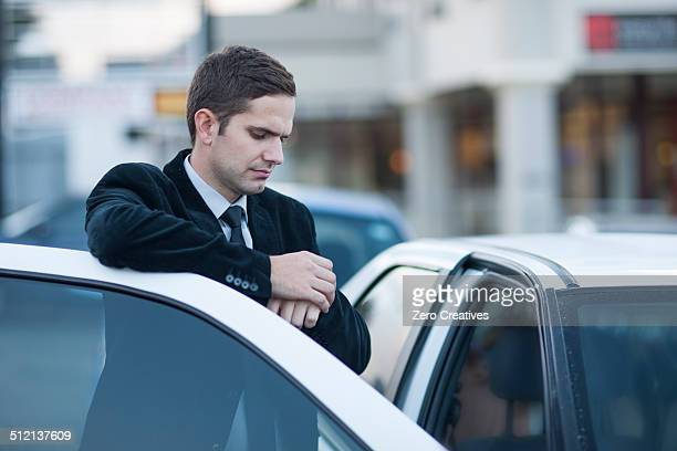 Mid adult businessman looking at watch in city traffic jam
