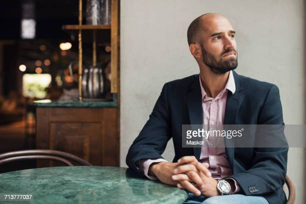 Mid adult businessman looking away white sitting at table in restaurant