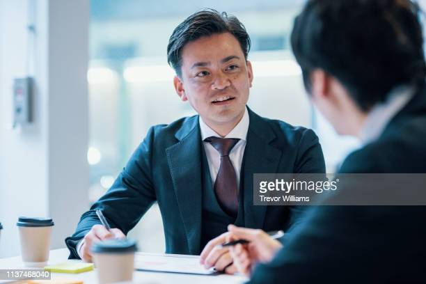 mid adult businessman meeting with a client in a corporate office - 日本人 ストックフォトと画像