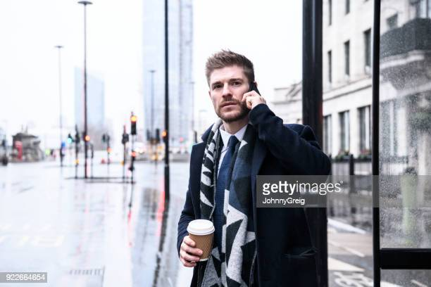 Mid adult businessman on cell phone in bus shelter with coffee
