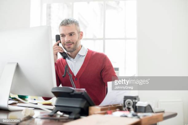 mid adult businessman on phone in office looking at computer monitor - cardigan sweater stock pictures, royalty-free photos & images