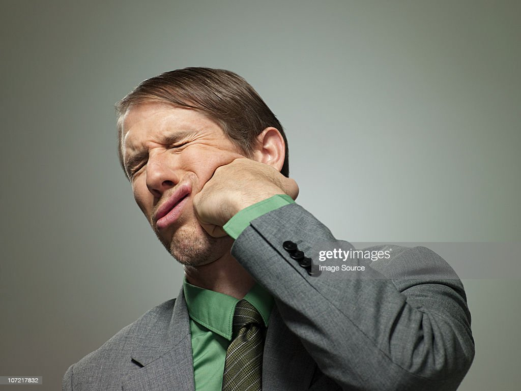 Mid adult businessman punching himself in face, portrait : Stock Photo