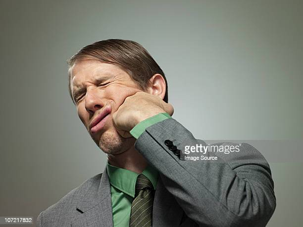 Mid adult businessman punching himself in face, portrait