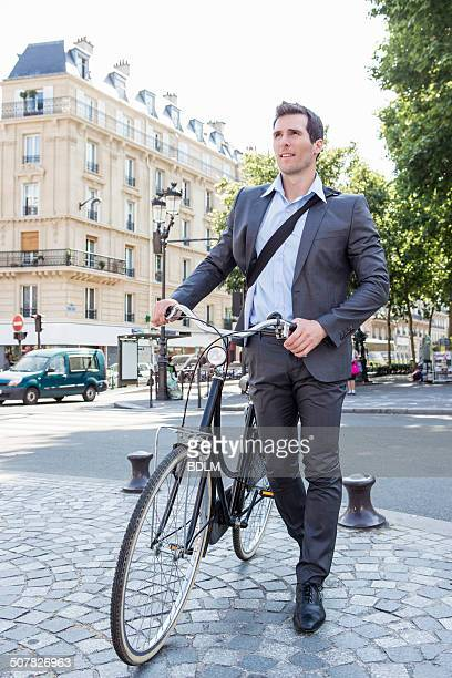 Mid adult businessman pushing bicycle over cobbles, Paris, France