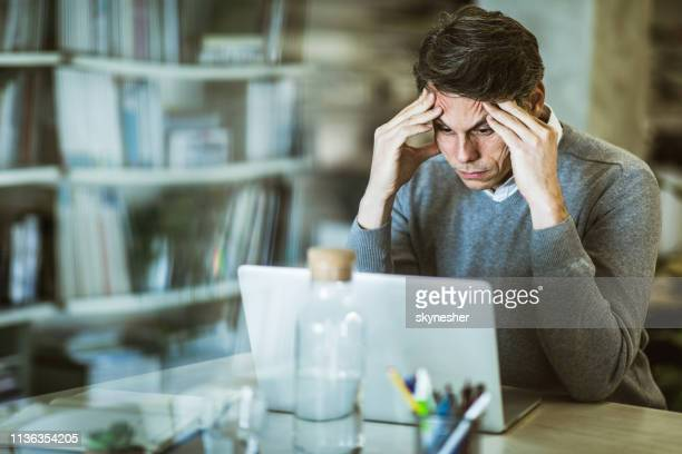 mid adult businessman reading problematic e-mail on laptop at home office. - economist stock pictures, royalty-free photos & images