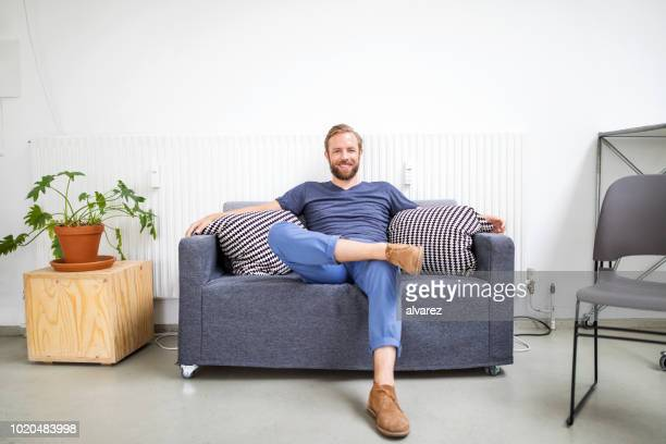 mid adult businessman relaxing on sofa - divano foto e immagini stock