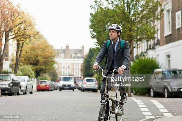 Mid adult businessman riding bicycle on street