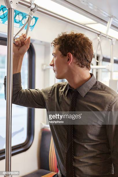 mid adult businessman staring out of train carriage window - heshphoto stock pictures, royalty-free photos & images