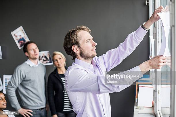 Mid adult businessman sticking paper on window with colleagues looking at him in office