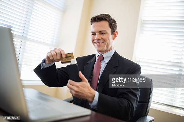 Mid Adult Businessman Swiping Credit Card Using Reader