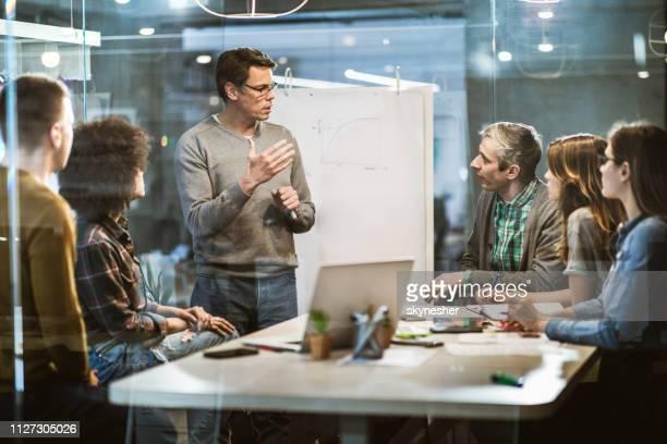 mitte adult geschäftsmann im gespräch mit seinen kollegen auf präsentation im büro. - kommunikation stock-fotos und bilder