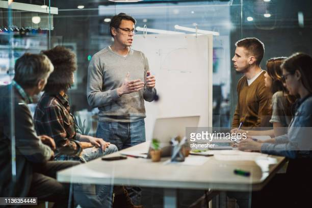 mid adult businessman talking to his colleagues on presentation in the office. - new business stock pictures, royalty-free photos & images