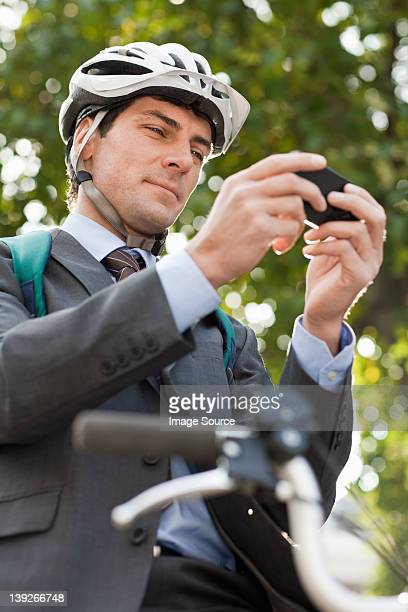 mid adult businessman using cellphone to text on bicycle - cycling helmet stock photos and pictures
