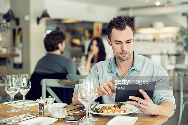 Mid adult businessman using digital tablet while having lunch at table in restaurant