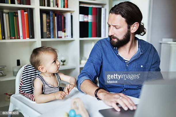 Mid adult businessman using laptop while looking at baby boy at home