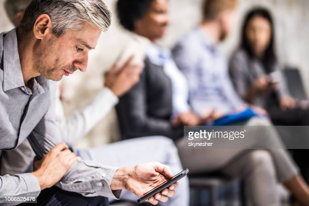 mid adult businessman using mobile phone while waiting for a job interview. - job search stock pictures, royalty-free photos & images