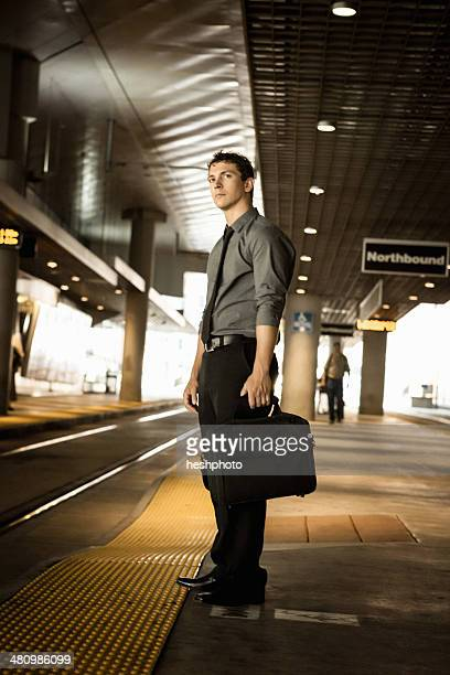 mid adult businessman waiting for train at station - heshphoto photos et images de collection