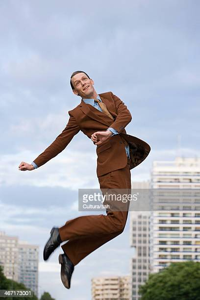 mid adult businessman wearing brown suit jumping - brown suit stock photos and pictures