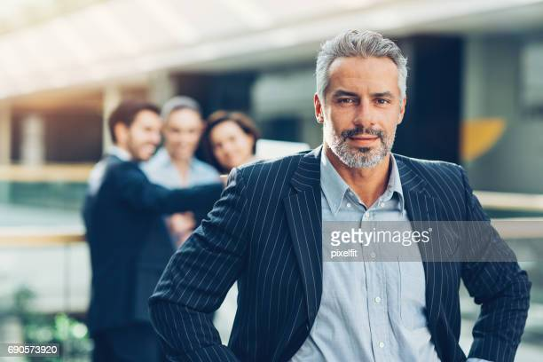 Mid adult businessman with his team behind