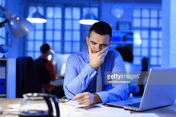 mid adult businessman working late - failure stock photos and pictures