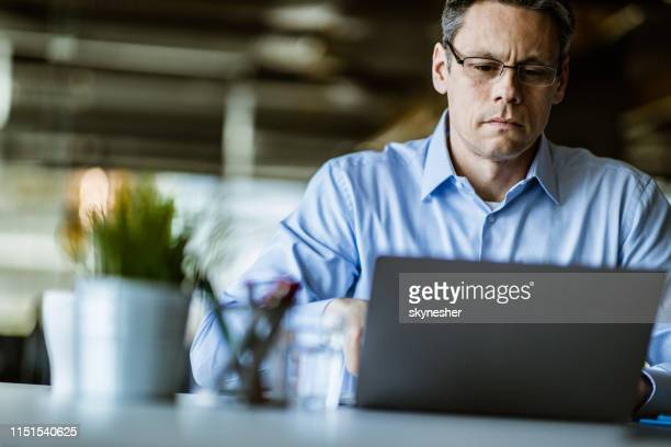 mid adult businessman working on a computer in the office. - economist stock pictures, royalty-free photos & images