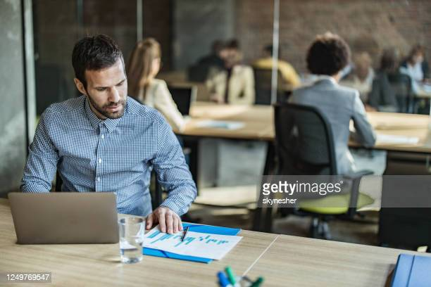 mid adult businessman working on computer and reports at full office. - incidental people stock pictures, royalty-free photos & images