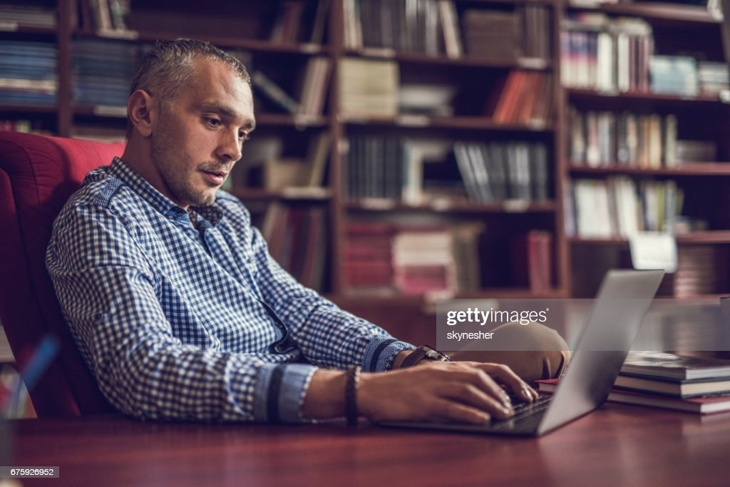 Mid adult businessman working on laptop at home library. : Stock Photo