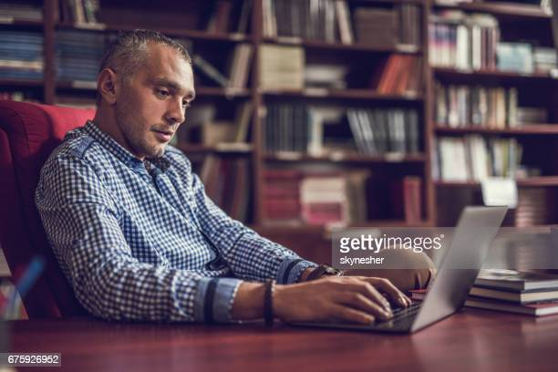Mid adult businessman working on laptop at home library.