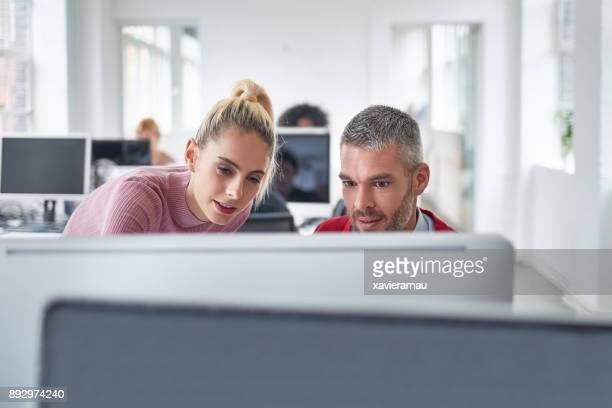 mid adult businessman working together with his colleague in the office - doing a favor stock pictures, royalty-free photos & images