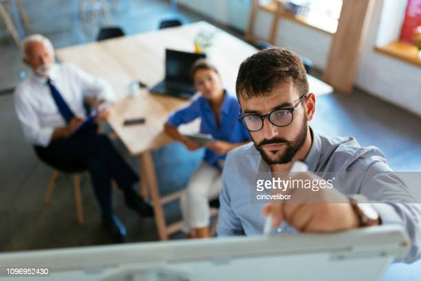 mid adult businessman writing a business plan on whiteboard during a meeting at conference room - business plan stock pictures, royalty-free photos & images
