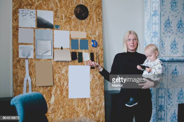 Mid adult businesswoman carrying baby girl while giving presentation in creative office