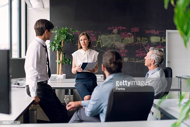 Mid adult businesswoman communicating coworkers