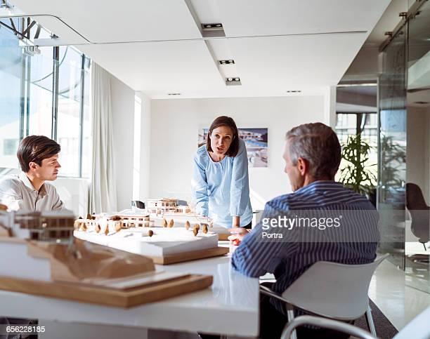 mid adult businesswoman communicating with team - 建築模型 ストックフォトと画像