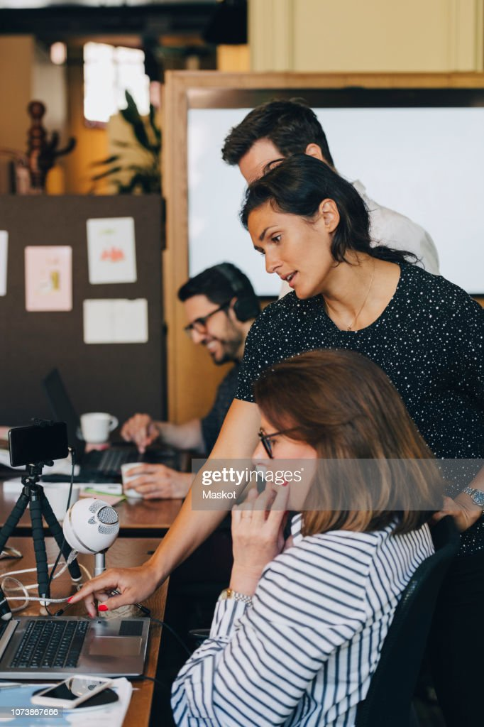 Mid adult businesswoman discussing with team over laptop in office : Stock-Foto